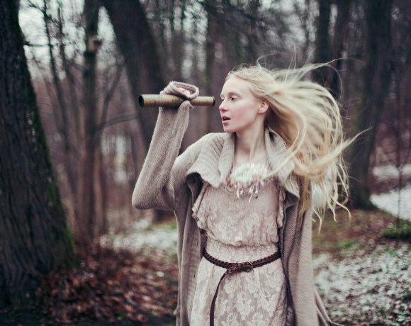 blond girl running in a forest in winter with binoculars