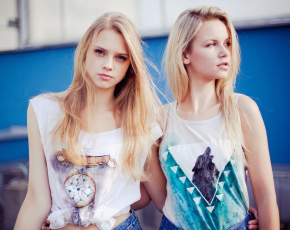 two blond models in t shirts against a blue wall