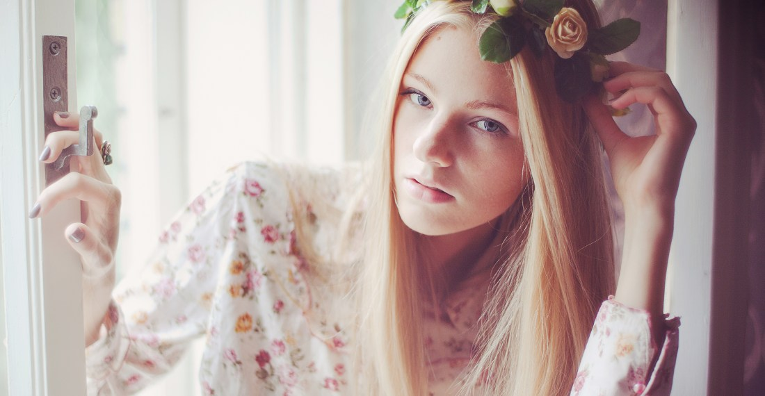 portrait of a blond girl by a window with a flower crown on