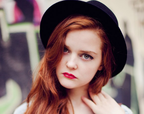 redhead girl with red lipstick and fedora hat in front of grafitti wall