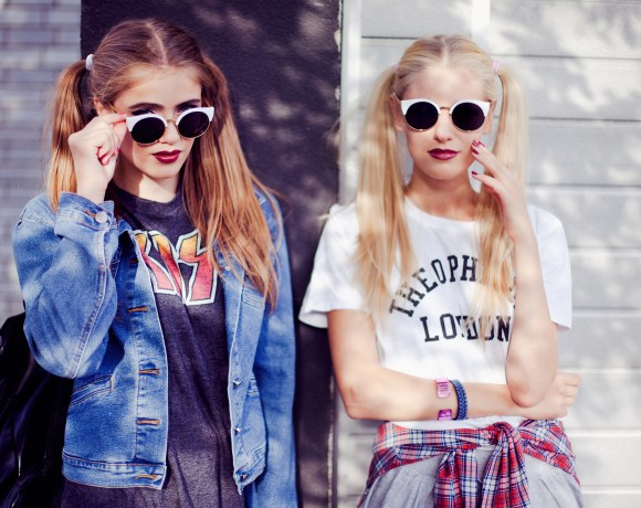 two girls in 90's rock'n'roll outfits and sunglasses standing under shadows