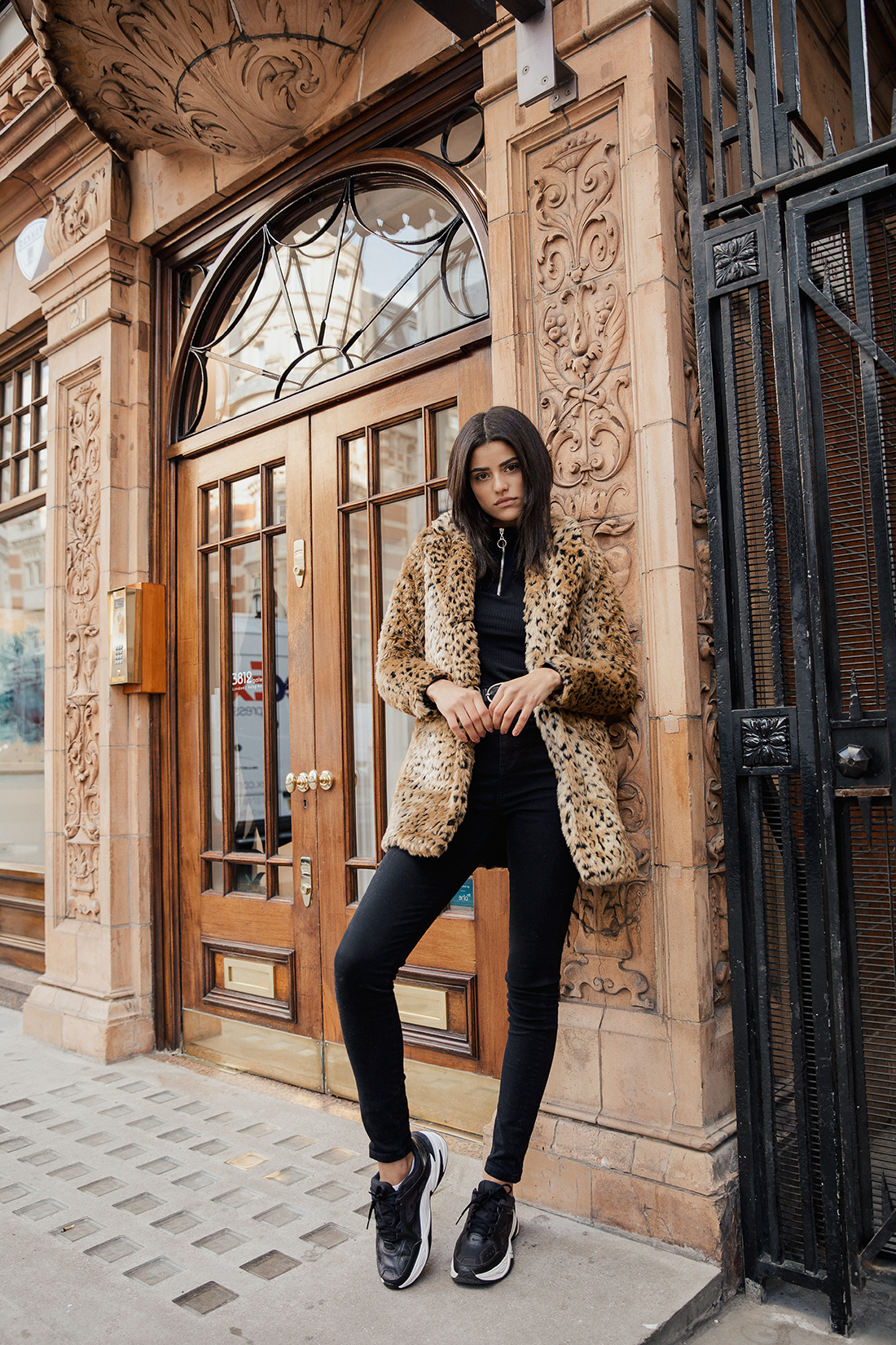full length fashion image of a black haired model wearing black jeans and a leopard coat leaning against a brown building