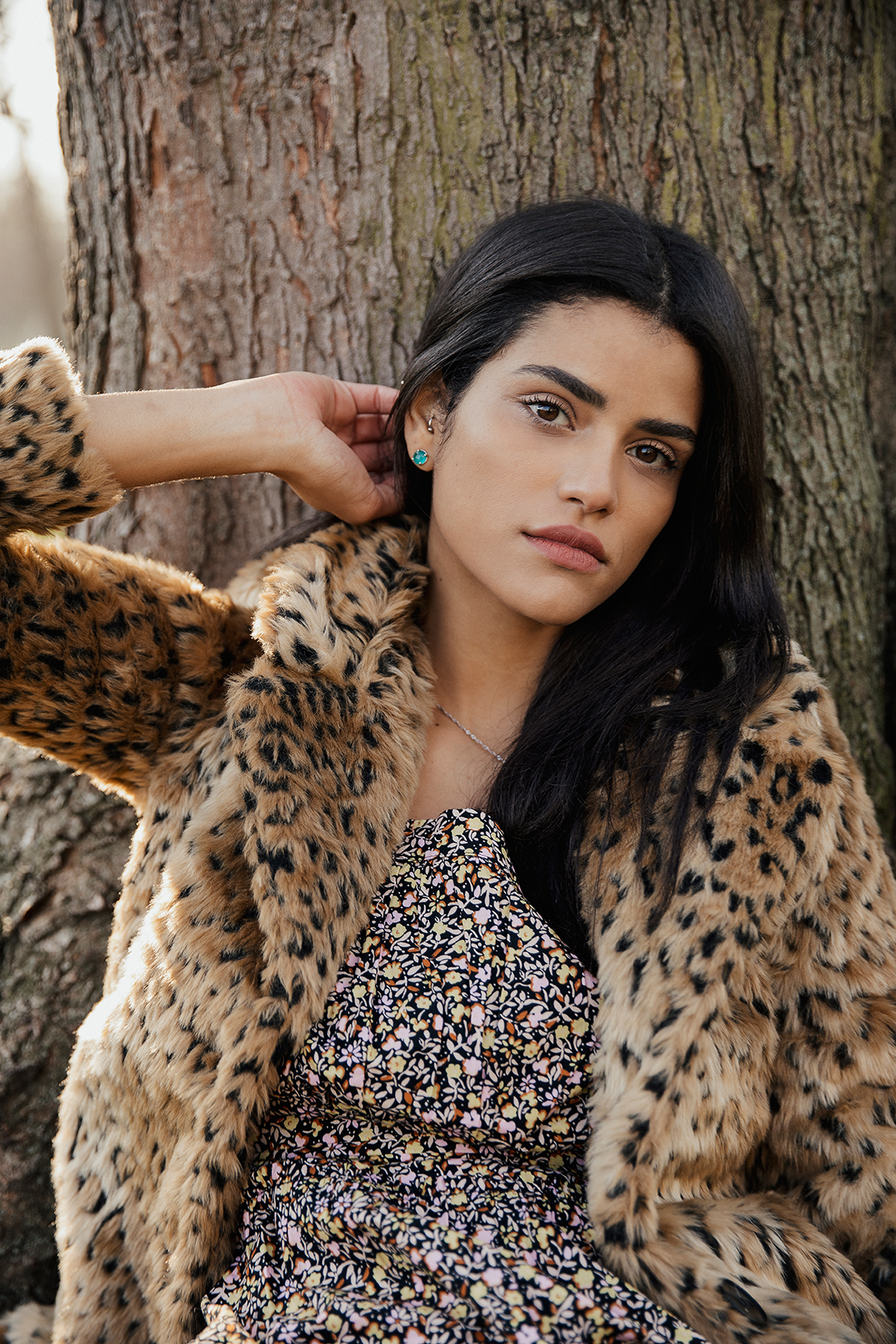 portrait of a  Brazilian model sitting by a tree in a leopard print coat taken by London based fashion and portraits photographer Ailera Stone