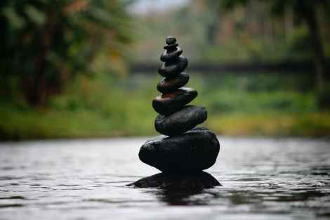 live a balanced life: black stackable stone decor at the body of water
