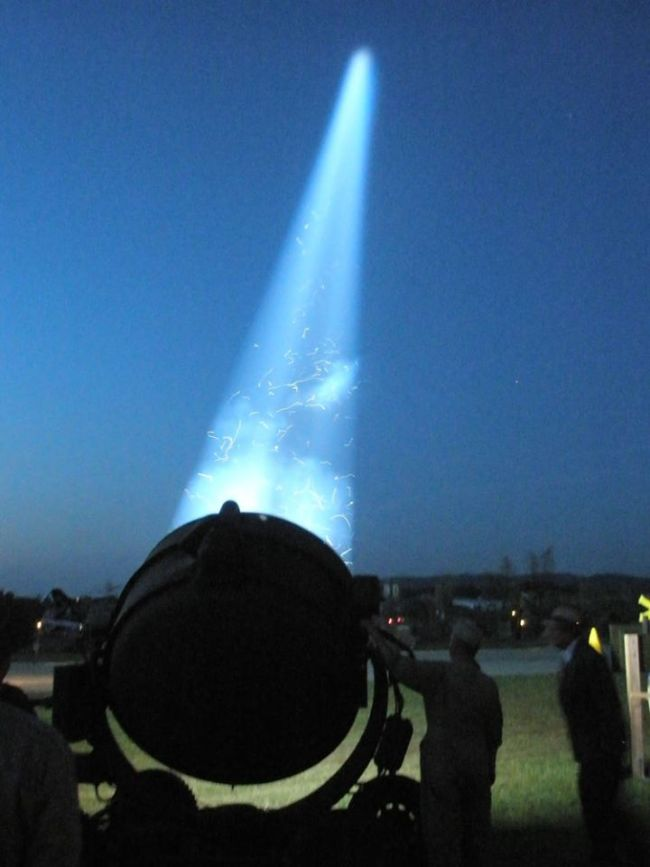 "alt=""Searchlights Lit Up The Night Sky And The Carnival Midway"""