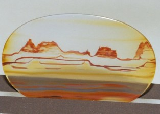 A pale yellow agate cabochon with bumpy orange bands that look like mountains or sand dunes.
