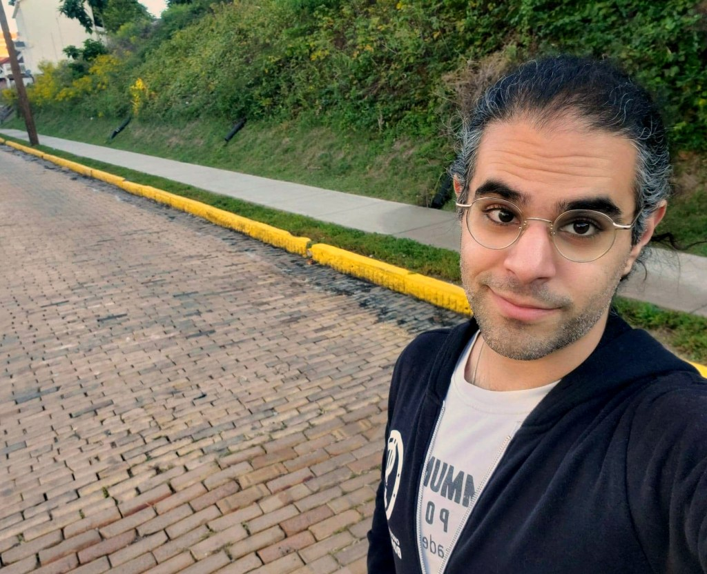 Eli Namay (a man with salt and pepper hair and glasses) standing in a paved pathway with Greenery in the background