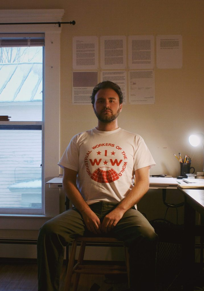 Jack Langdon, sitting in a chair, wearing a 'workers of the world unite' T-Shirt