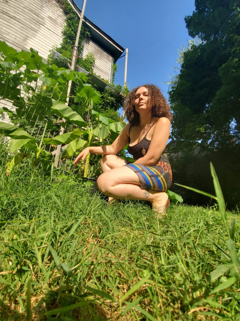 Looking upwards at Ruby Pinto who is kneeling in grass in her garden
