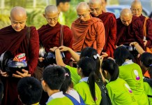 People offer alms to monks