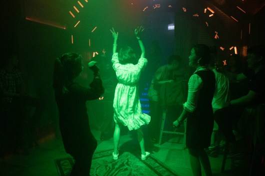 A girl in white dress was dancing in the middle of the dancing floor under the green spotlight.