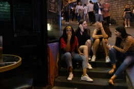 Four girls were chatting while sitting on a staircase outside a bar in Lan Kwai Fong. There was a girl holding a bottle of Smirnoff ICe.
