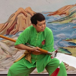 A woman displaying the use of broadsword in Kung Fu