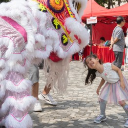 A little girl happily interacting with the lion-dance performers in a workshop