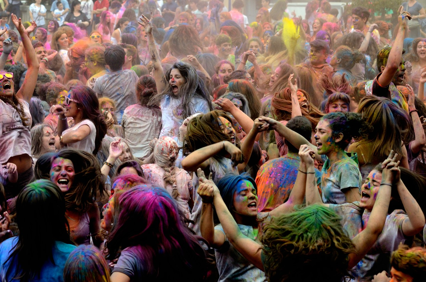 Representational image of crowd playing Holi covered in coloured powder.