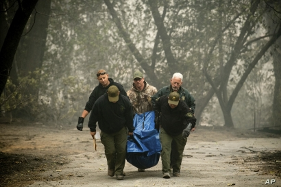 FILE - In this Saturday, Nov. 10, 2018 file photo, Sheriff's deputies recover the remains of a victim of the Camp Fire in Paradise, Calif. As California counties face the prospect of increased utility power shut-off meant to prevent wildfires,…