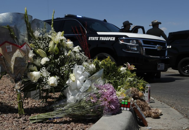 Flowers adorn a makeshift memorial near the scene of a mass shooting at a shopping complex in El Paso, Texas, Aug. 4, 2019.
