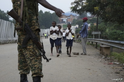 FILE - School-going pupils from the Democratic Republic of Congo cross the Mpondwe border point separating Uganda and the DRC, Aug. 14, 2019.