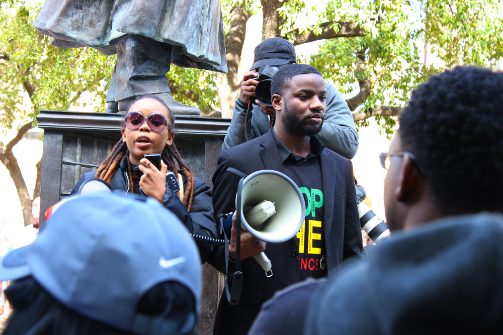 One of the march organizers, X, speaks to the crowd.