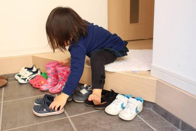 玄関で自分の靴を並べる子供2