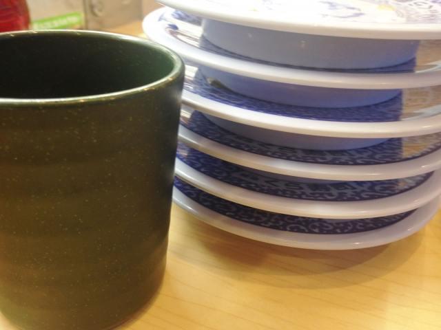 回る寿司の皿と湯呑