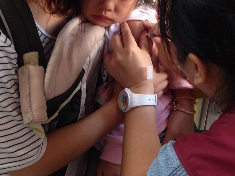 孩童在施打疫苗的過程中,護理人員會與他們談天建立信任關係,降低孩童心中的恐懼。攝影/高凡淳