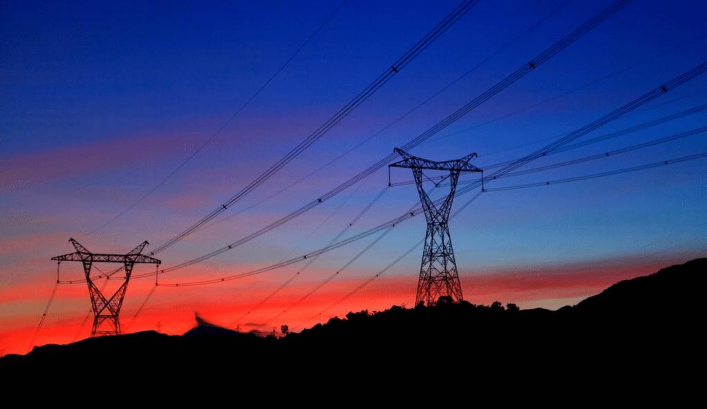 Fotografía en color de torres de transmisión de energía al atardecer.