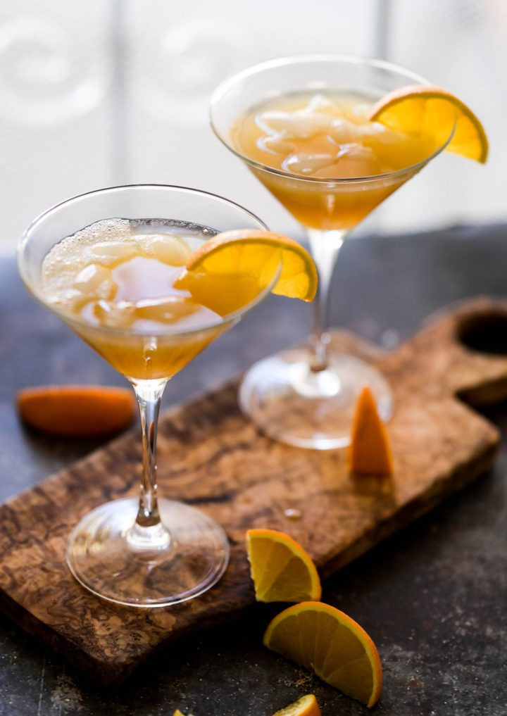 Photo of two cocktails in a martini glass with an orange twist garnish.