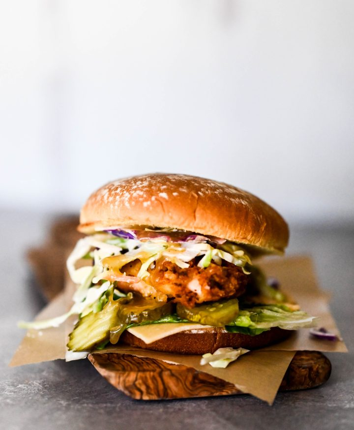 Portrait photo of a chicken sandwich dripping with honey slaw.