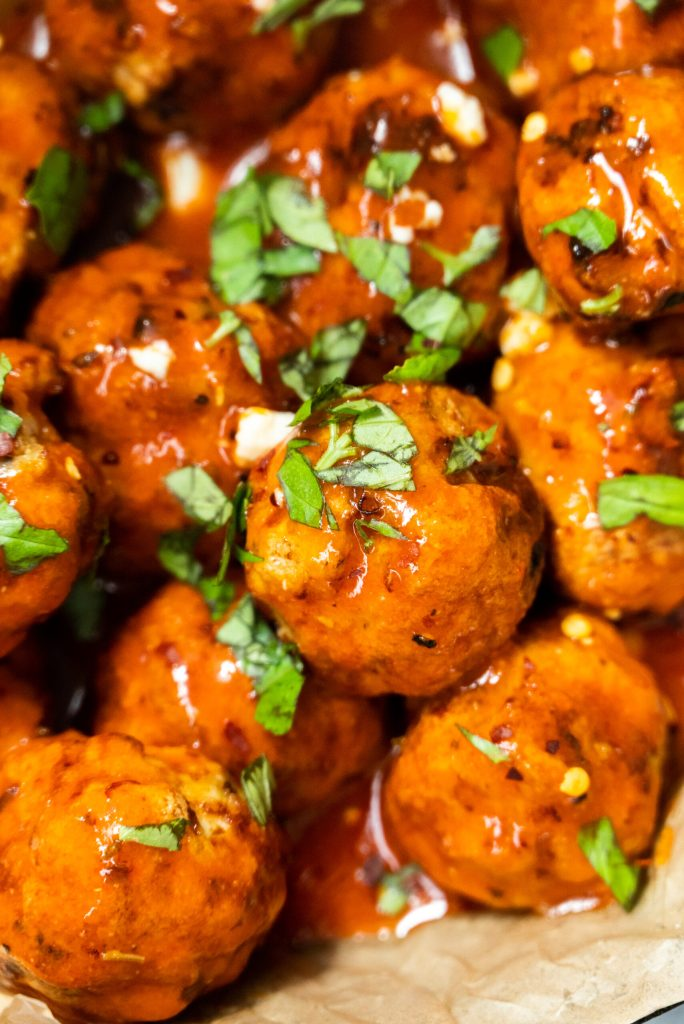 Tight photo of buffalo meatballs with chopped basil
