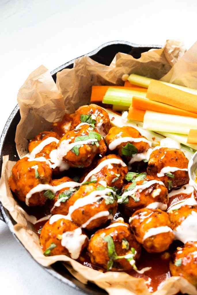 Buffalo meatballs in a dish with carrots and celery.