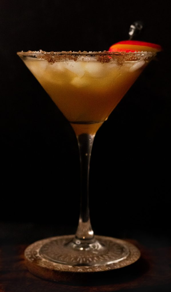 A martini glass with the apple cider martini and an apple garnish.