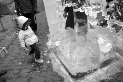 A little girl kicks at a chunk of ice near an ice scupture.