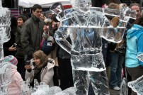 People pose and take pictures with ice sculptures.