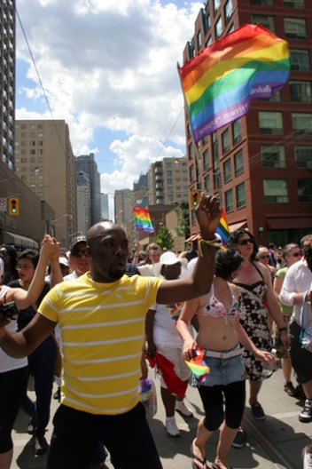 A man dances with a rainbow flag on Carlton StreetSaturday, June 30th, 2012