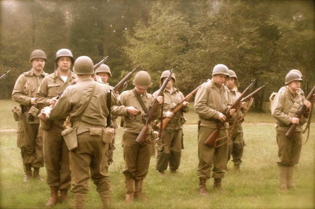 T/4 Gray of Fox Company, 325th G.I.R., 82nd AB inspects the squad's arms.