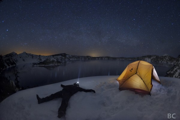 man lying down in snow at night