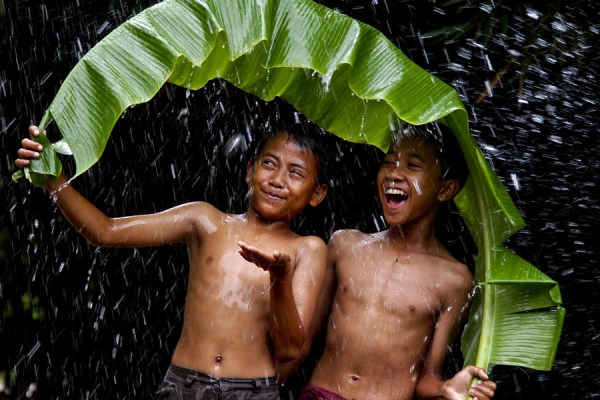 two boys enjyoing rain