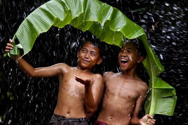 two boys enjyoing rain