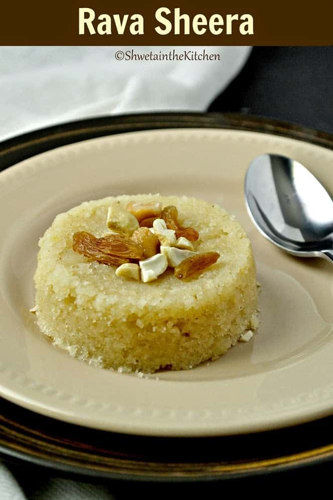 A around of rava sheera served on a plate with a spoon and topped with nuts and raisins