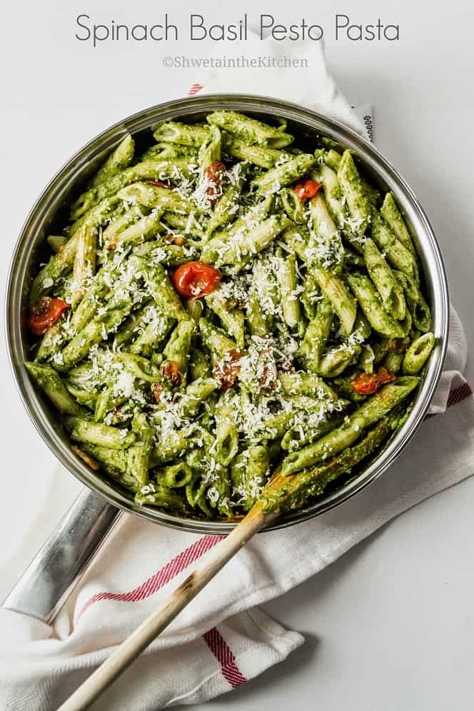 Spinach and basil pesto pasta in a pan with roasted tomatoes