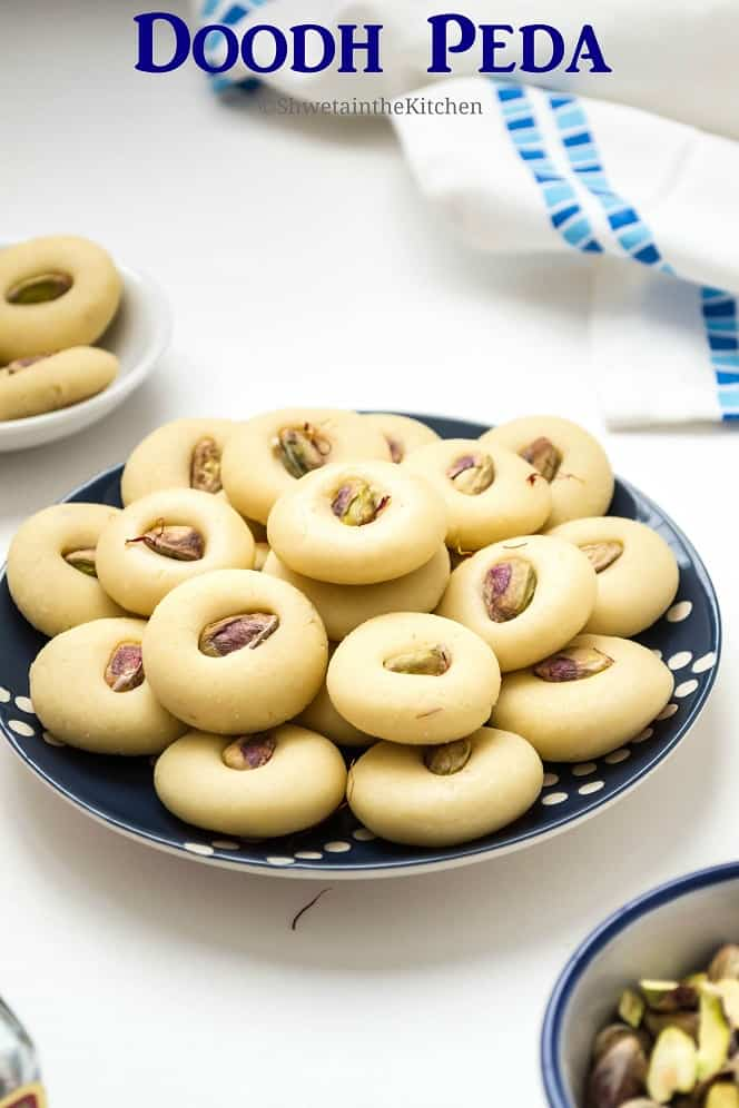 Doodh peda served on a plate next to a bowl of pistachios