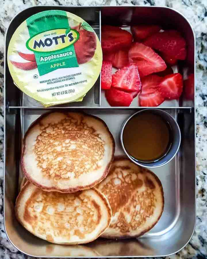 Eggless Pancakes with maple syrup, applesauce and sliced strawberries
