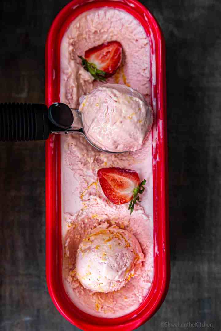 Tub of strawberry icecream with cut strawberry