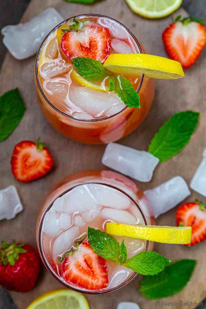 Top view of two strawberry lemonade glasses garnished with lemon slices, strawberry and mint