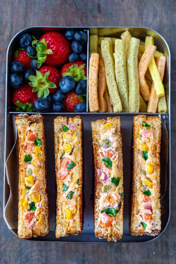 Lunch box packed with vegetable sandwich, straws and berries