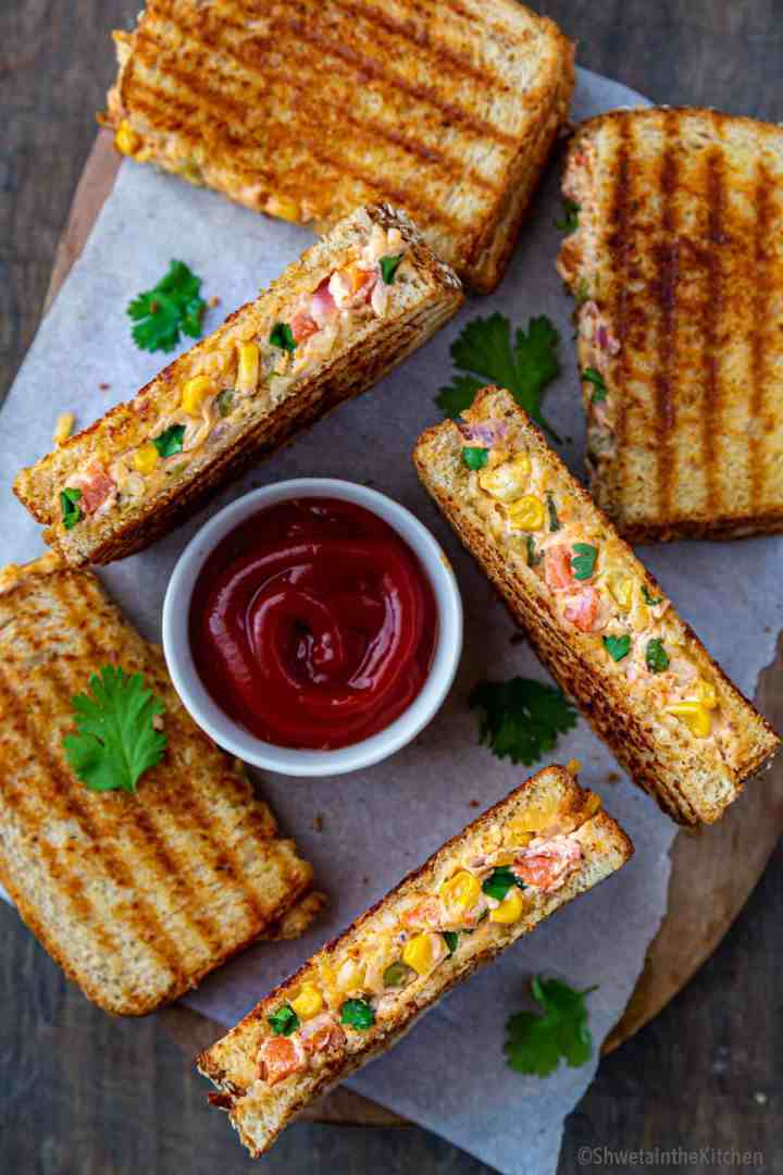 bowl of ketchup surrounded bygrilled veg sandwich with