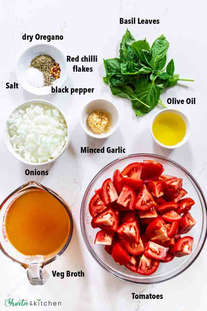 Ingredients for Tomato Basil soup laid out in bowls on white marble surface