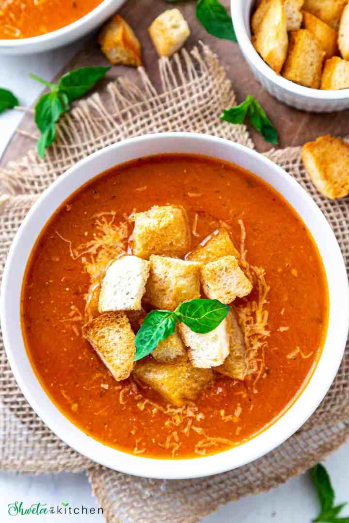 Bowl of Tomato basil soup with crouton and basil leaves placed on burlap cloth