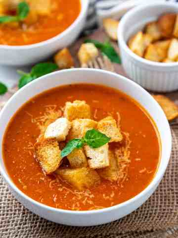 Bowl filled with vegan tomato basil soup toppped with croiton and basil